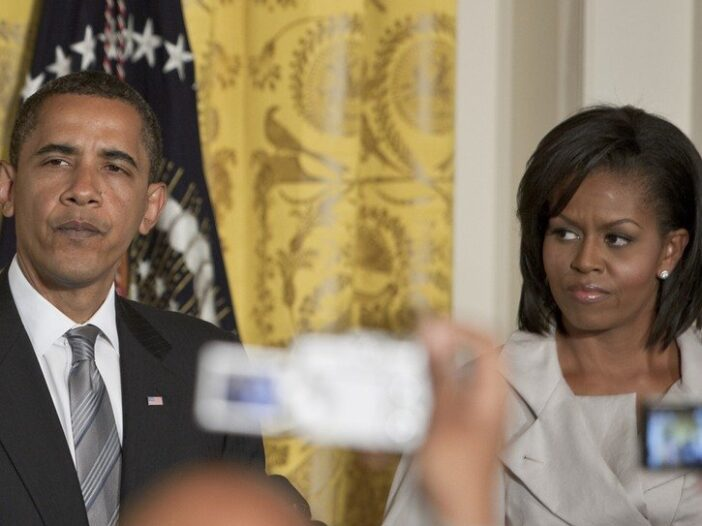 Barack Obama on the left, Michelle Obama on the right, but with scowls on their faces at a press conference.