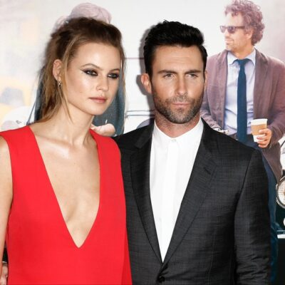 """Behati Prinsloo on the left in a low-cut red dress and Adam Levine on the right attending the New York premiere of """"Begin Again"""","""