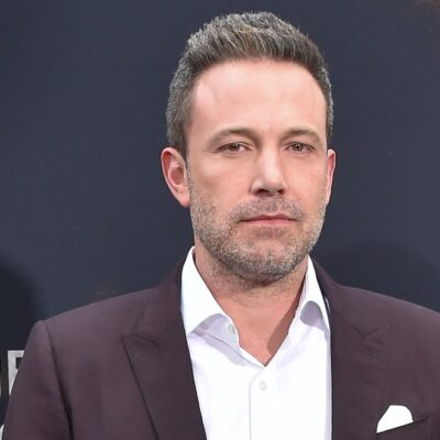 Ben Affleck in a maroon suit standing in front of a black background