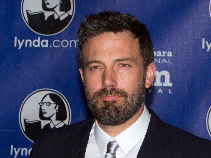 Ben Affleck in a suit, in front of a blue background.