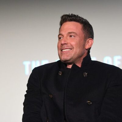 Ben Affleck smiles in a buttoned up black coat against a neutral background
