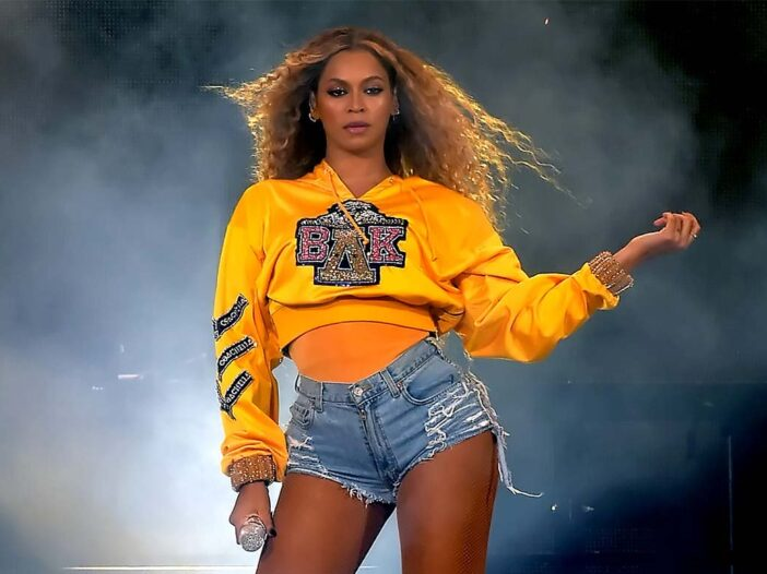 Beyonce performing in a yellow shirt and jean shorts