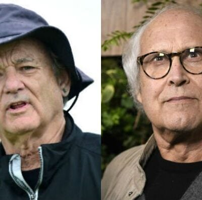 Bill Murray in a black jacket and rain hat on a golf course. Chevy Chase in a tan sweater and black