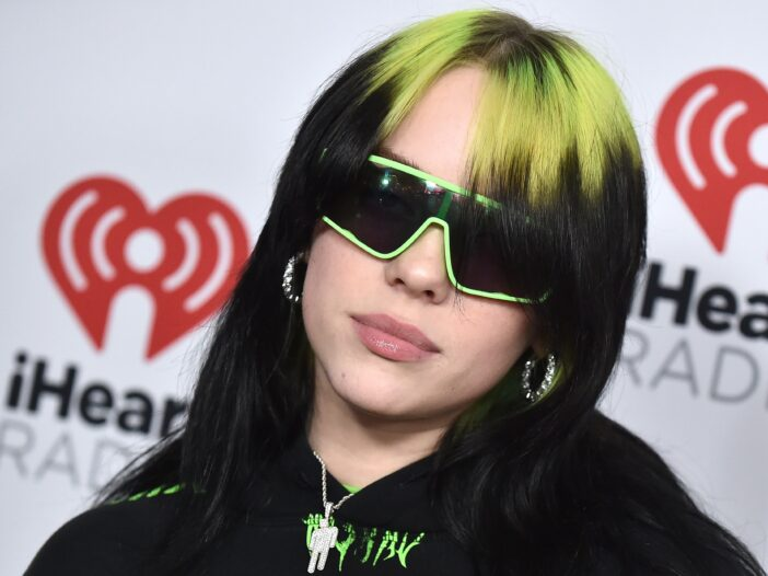 Billie Eilish with black and green hair with green sunglasses on