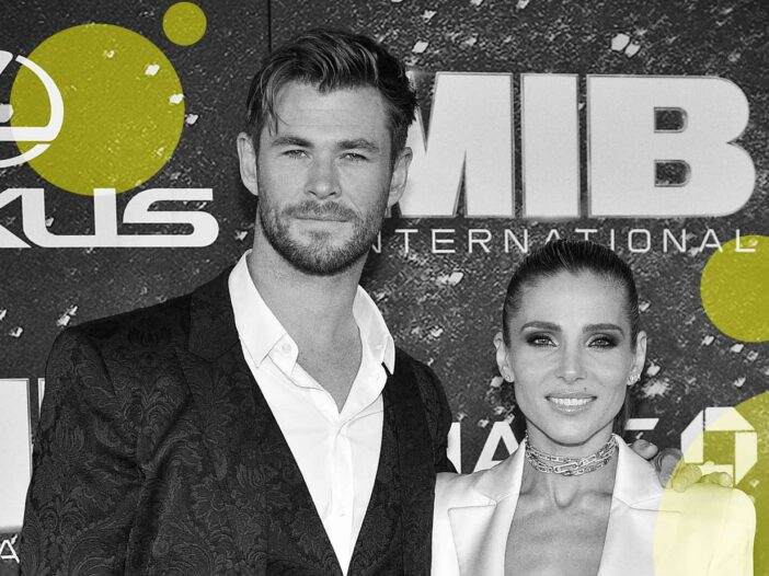 black and white photo of Chris Hemsworth in a patterned suit with wife Elsa Pataky in a white pantsu