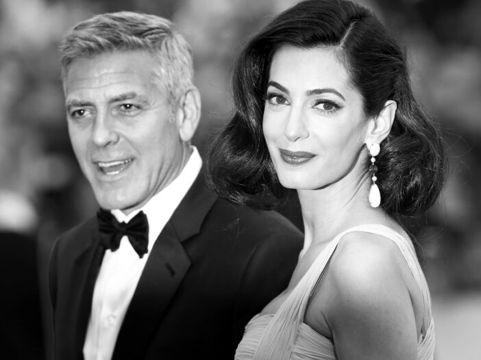 Black and white photo of George Clooney on the left and Amal Clooney on the right.