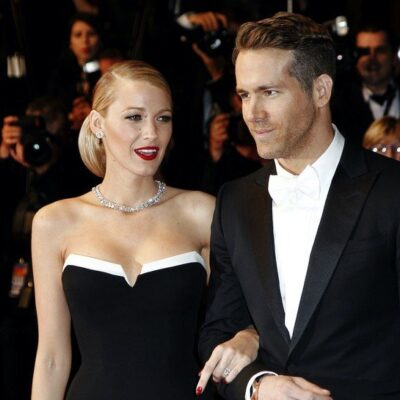 Blake Lively smiling in a black dress arm in arm with a smiling Ryan Reynolds in a tux and white tie