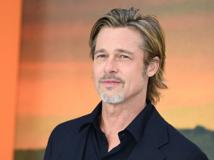 Brad Pitt in a black suit and shirt looking forward against an orange background