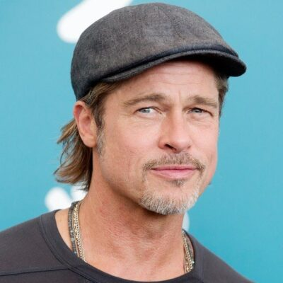 Brad Pitt slyly smiling for the camera wearing a hat.
