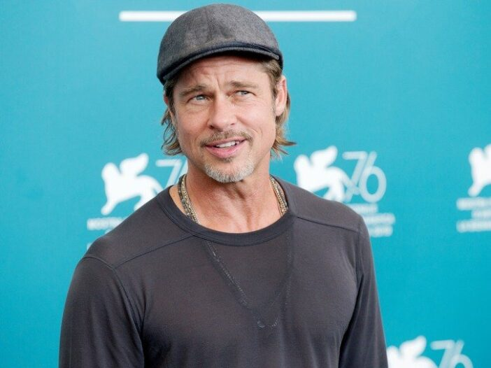 Brad Pitt smiles in a grey shirt against a blue background