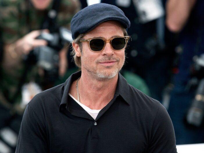 Brad Pitt smiling in a grey cap and black shirt