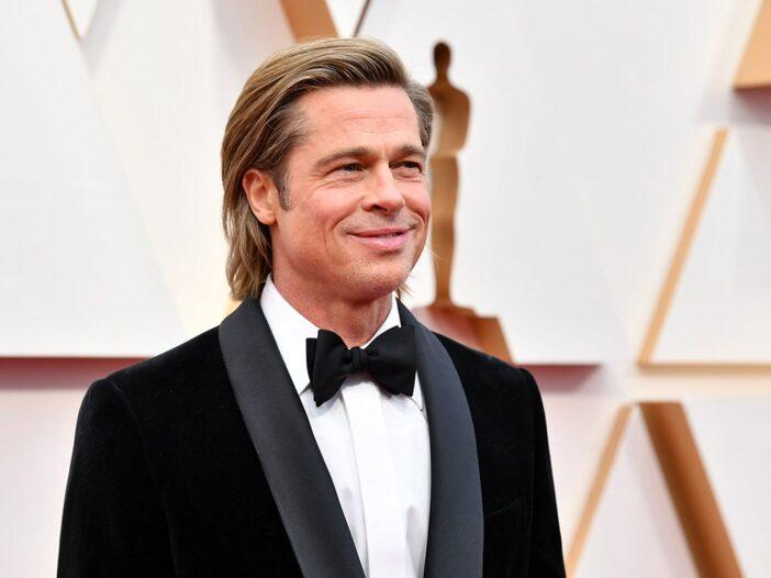 Brad Pitt smiling in a tuxedo at the Oscars