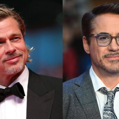 Brad Pitt wearing a black tux on the red carpet. Robert Downey Jr. wearing a gray suit on the red ca