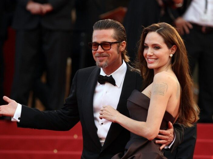 Brad Pitt, wearing a tux, walks with Angelina Jolie, wearing a strapless gown, on the red carpet