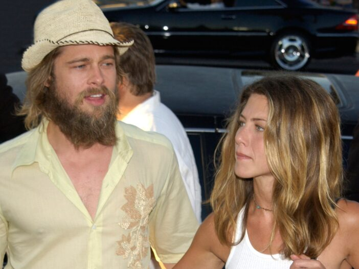 Brad Pitt with a long beard standing with Jennifer Aniston in a white tank top, when they were married.