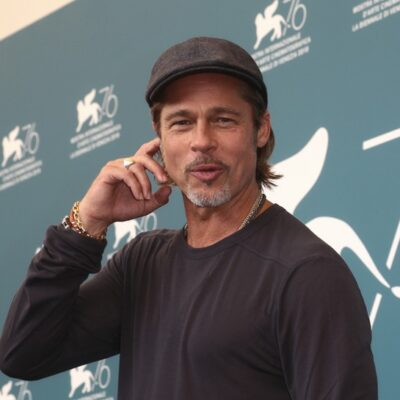 """Brad Pitt with his finger on his ear making a """"what?"""" face."""