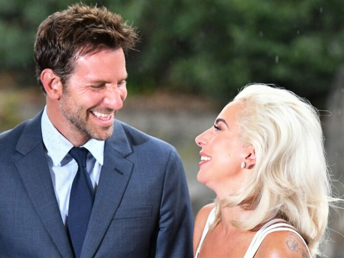 Bradley Cooper on the left, looking at Lady Gaga on the right, both laughing.