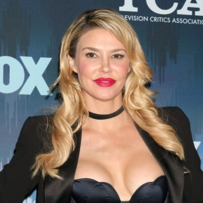 Brandi Glanville smiles in a black dress and jacket against a blue background