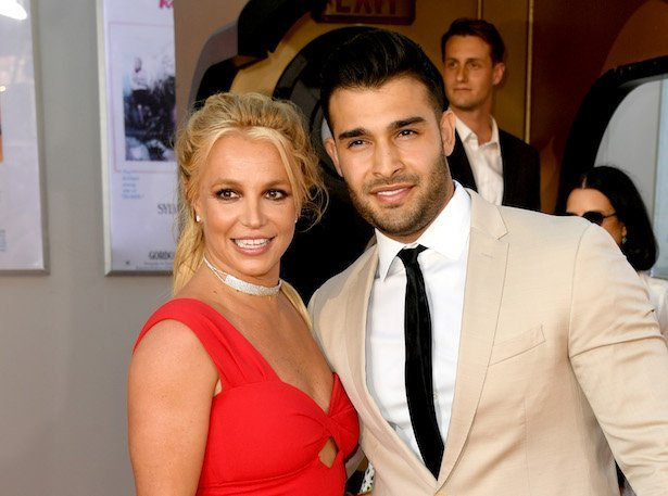 Britney Spears in a red dress smiling next to Sam Asghari in a tan suit