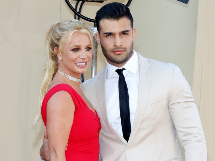 Britney Spears smiling in a red dress with Sam Asghari in a white suit