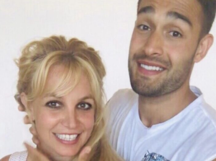 Britney Spears, wearing a crop top, poses with Sam Asghari, in a white t shirt