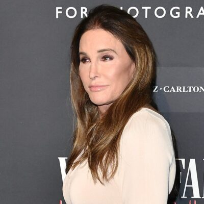 Caitlyn Jenner smiles to her right dressed in a tan dress