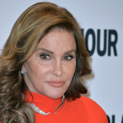 Caitlyn Jenner wears a red dress with her hair loose on the Glamour red carpet.