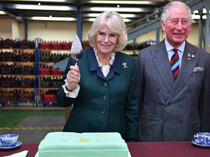 Camilla Paker Bowles holding a cake knife next to Prince Charles, behind a green cake