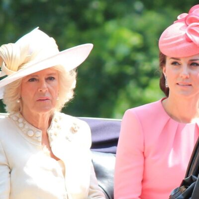 Camilla Parker Bowles in a white outfit and hat sitting with Kate Middleton in a pink outfit and hat