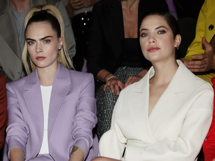 Cara Delevingne wearing a purple suit sitting front row with Ashley Benson, who's wearing a white su