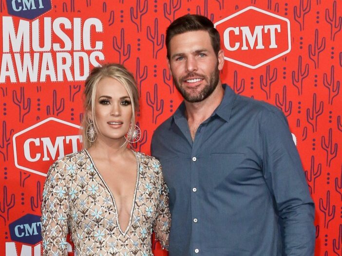 Carrie Underwood smiling in a sheer dress with husband Mike Fisher in a blue shirt