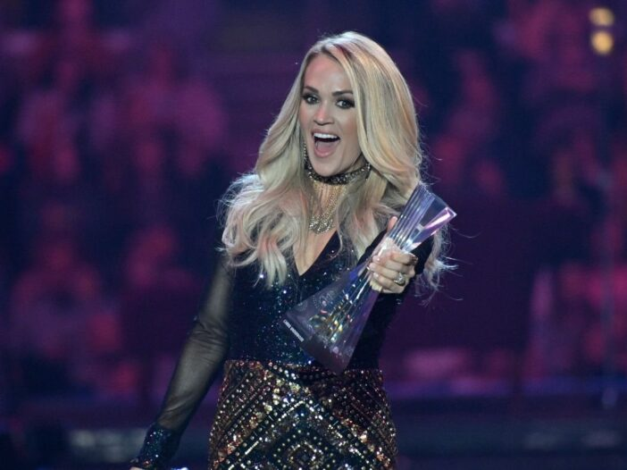 Carrie Underwood wearing a black dress on stage at the CMT awards