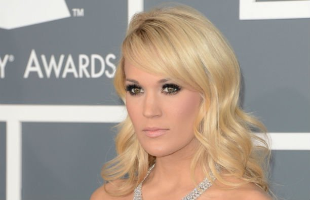Carrie Underwood wearing a silver dress on the red carpet