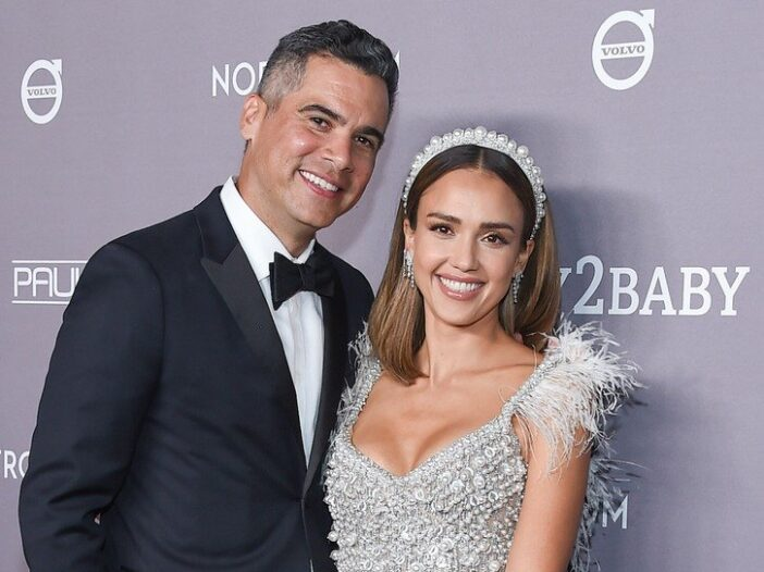 Cash Warren smiling in a tuxedo with his arm around his wife Jessica Alba in a silver dress