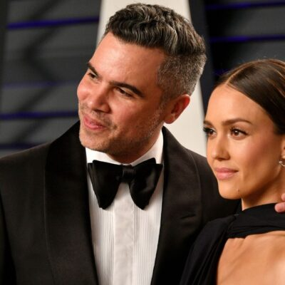 Cash Warren wearing a black tux standing with Jessica Alba, who is wearing a black dress, on the red
