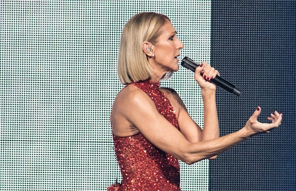 Celine Dion performing in a red, sparkly dress.
