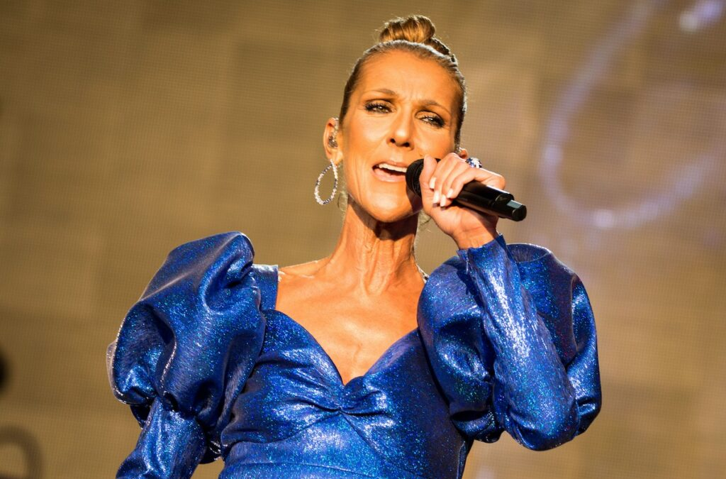 Celine Dion singing in a blue dress on stage