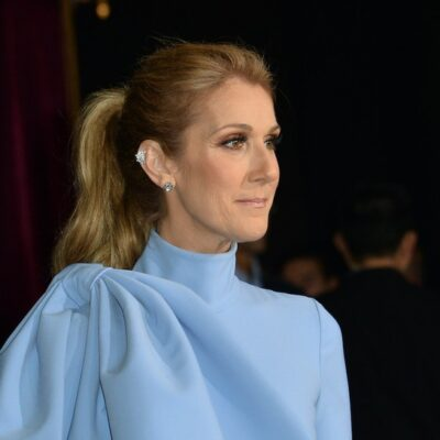 Celine Dion smiling in a light blue dress at a red carpet event