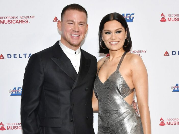 Channing Tatum wearing a black suit standing with Jessie J, who's wearing a silver dress, on the red
