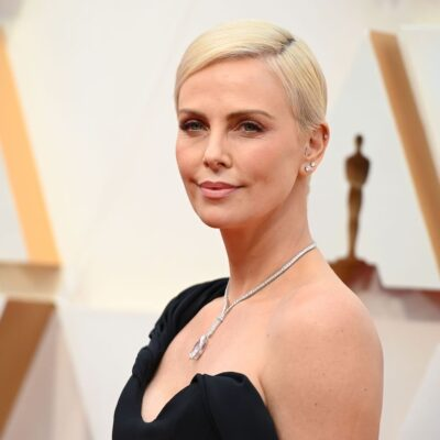 Charlize Theron smiling at the camera in a black dress at the 92nd Oscars for her role in Bombshell