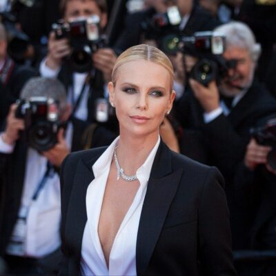 Charlize Theron wearing a black suit jacket and white shirt on the red carpet