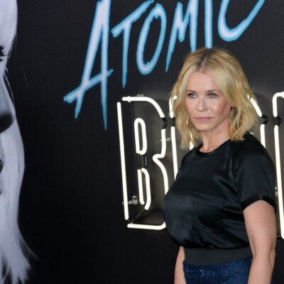 Chelsea Handler in a black top and blue pants posing in front of an Atomic Blonde Display