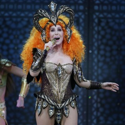 Cher performing on stage in an orange wig and gold and black costume.