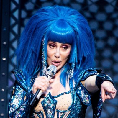 Cher wearing a blue wig and matching bodysuit performing live onstage