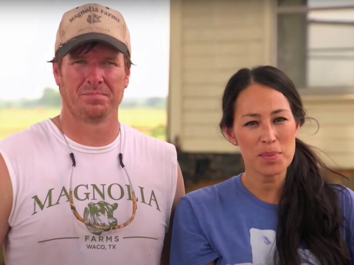 Chip Gaines in a white tank top, Joanna Gaines in a blue shirt in a still from Fixer Upper on HGTV