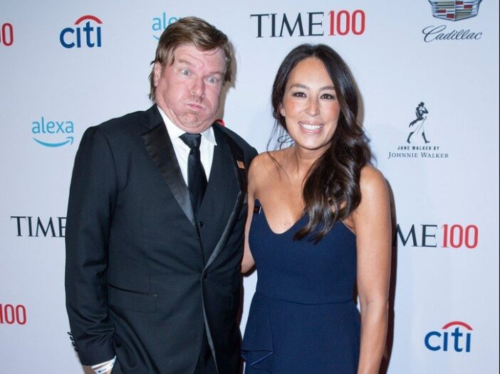 Chip Gaines on the left making a funny face, standing next to Joanna Gaines on the right, smiling,