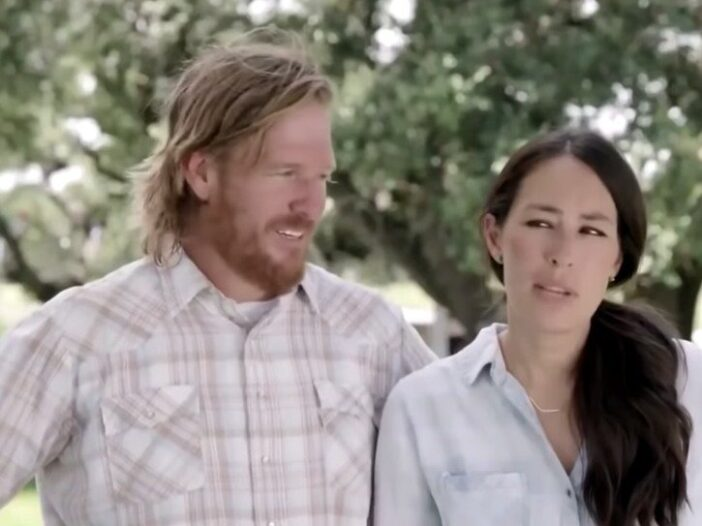 Chip Gaines wearing a checkered shirt standing with Joanna Gaines, in a blue top, on Fixer Uppers