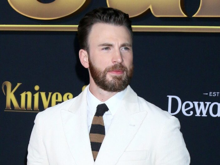 Chris Evans looking to his left in a white suit against a black background