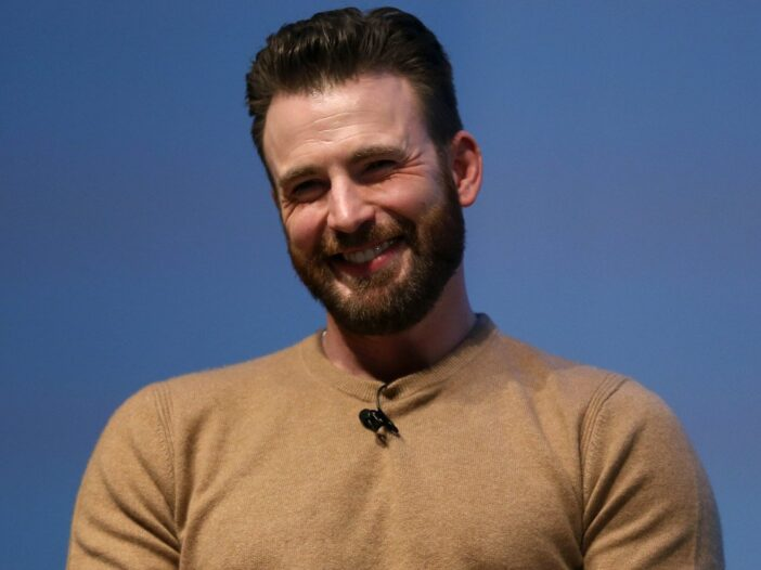 Chris Evans smiles and tilts his head dressed in a brown sweater against a blue background