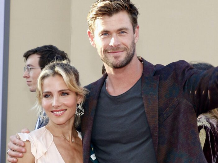Chris Hemsworth in a maroon jacket smiling with arm around wife Elsa Pataky in a tan dress